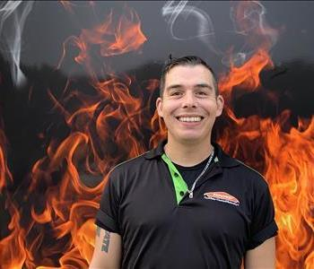 Crew member Joey standing against fake fire backdrop