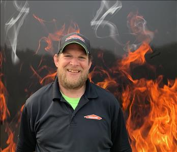 Project manager Nate Standing against fake fire backdrop