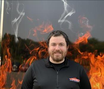 Nick, male job file coordinator. Standing against a fake fire backdrop