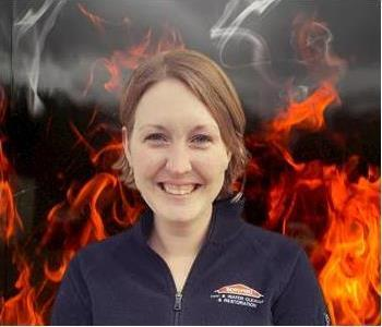 Crew member Susan standing against fake fire backdrop