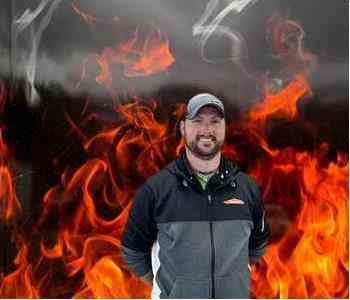 Casey, male crew chief smiling and standing against fake fire backdrop