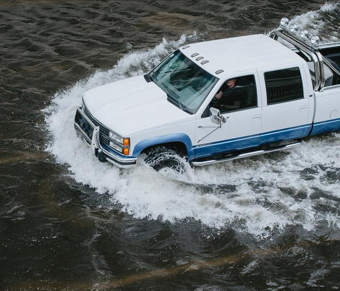 Truck driving through deep flood waters